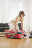 Germany, Leipuig, Woman kneeling on suitcase, smiling, portrait