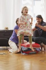 Deutschland, Leipzig, Mädchen springen Vater und Mutter packen Koffer