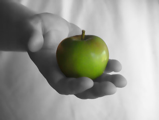 Hand holding a healthy juicy green apple