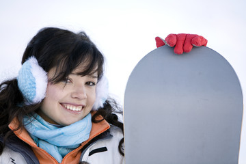 Lifestyle image of  young adult  snowboarder girl