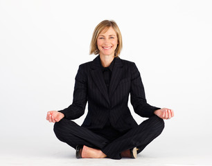 Mature businesswoman meditating on the floor