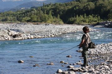 jeune garçon pêchant dans une rivière