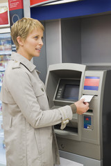 Woman receiving a transaction slip from an ATM