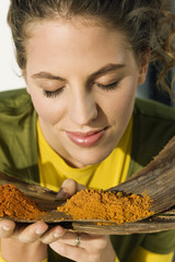 Close-up of a woman smelling spices