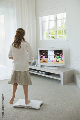 Girl doing step aerobics and watching TV