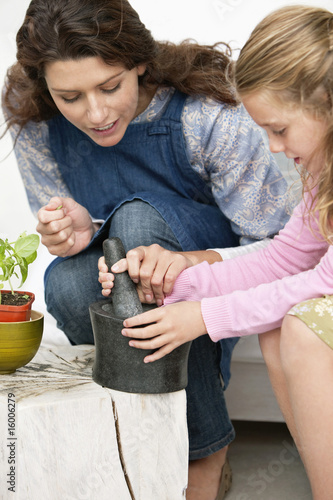 Women and her daughter with a mortar and pestle