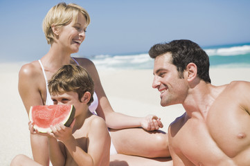 Boy eating a watermelon with his parents on the beach
