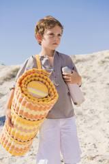 Boy carrying mat on the beach