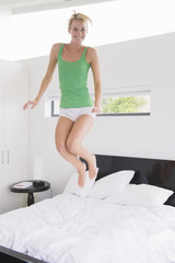 Woman jumping on the bed