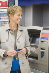 Woman holding a credit card and standing in front of an ATM
