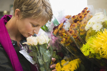 Woman holding a bouquet of flowers in a florist shop