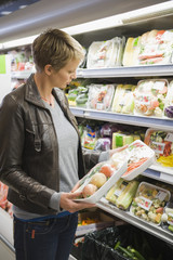 Woman buying packed food in a supermarket