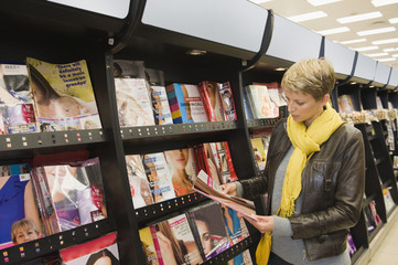 Woman choosing magazines in a supermarket