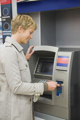 Woman inserting a credit card into ATM