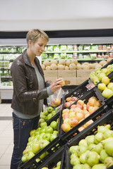 Woman buying apples in a supermarket