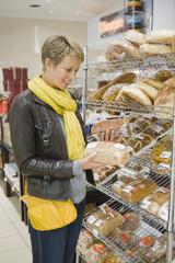 Woman choosing breads in a supermarket