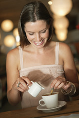 Woman adding milk in coffee in a cafe