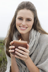 Woman holding a lit candle and smiling