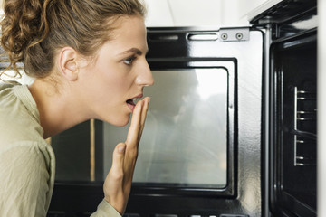 Woman looking shocked near an oven