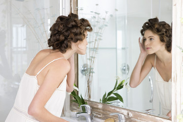 Woman examining her face in the mirror