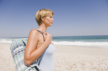 Woman carrying a mat on the beach