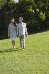 Couple walking on grass and smiling