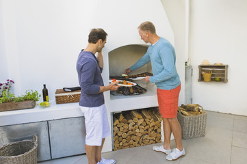 Two men cooking kebab at fireplace