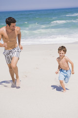 Man running with his son on the beach