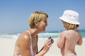 Woman having fun with her daughter on the beach