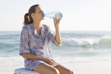 Woman sitting on an ice box and drinking water on the beach
