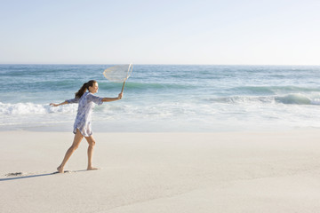 Woman carrying a fishing net on the beach