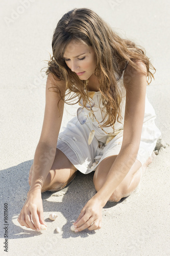 Woman playing with seashells on the beach