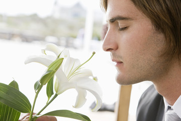 Close-up of a groom smelling a lily flower