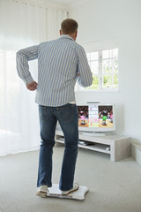 Man doing step aerobics and watching TV