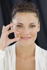 Portrait of a woman holding an Omega-3 capsule