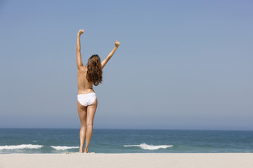 Rear view of a woman standing on the beach with her arms raised