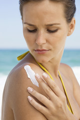 Woman applying suntan lotion on her shoulder