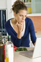 Woman reading a recipe on a laptop in the kitchen