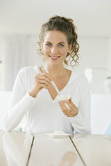 Woman mixing white clay for facial mask