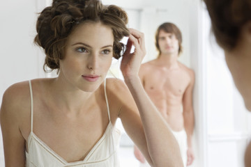 Woman using curlers with her boyfriend in the background