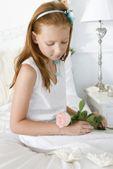 Girl holding a flower on the bed