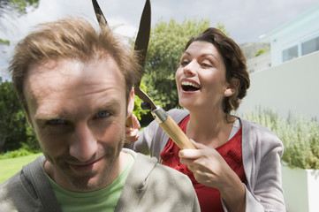 Woman cutting man's hair with a hedge clipper