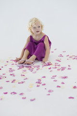 Girl sitting with flower petals scattered around her