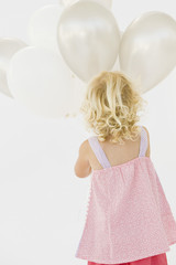 Rear view of a girl holding balloons