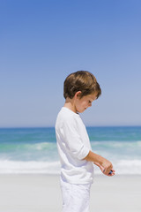 Boy holding a shell on the beach