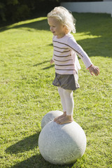 Girl standing on a round stone