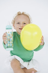 Baby boy holding a balloon and a baby bottle
