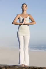 Woman practicing yoga on a boardwalk