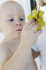 Baby boy holding a bunch of grapes