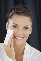 Woman cleaning her face with a tissue paper